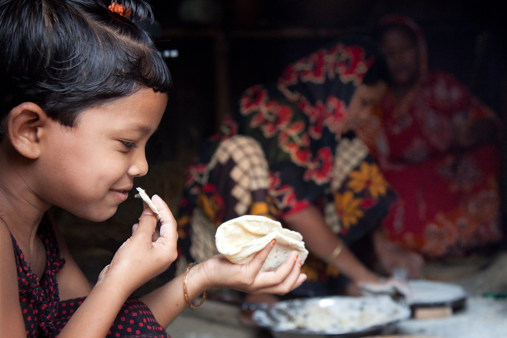 A little girl eats a freshly made roti while the women of her family prepare more, at her home in the village of Chapor, in the district of Dinajpur, Bangladesh. (Photo: S. Mojumder/Drik/CIMMYT)