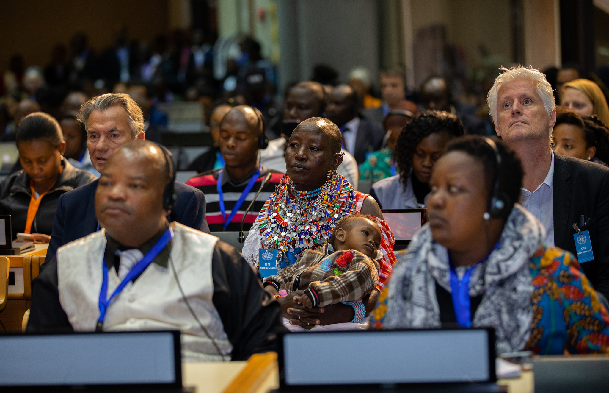 A Maasai woman holding a baby (center) attends the plenary session of the GLF Nairobi 2018. (Photo: Global Landscapes Forum)
