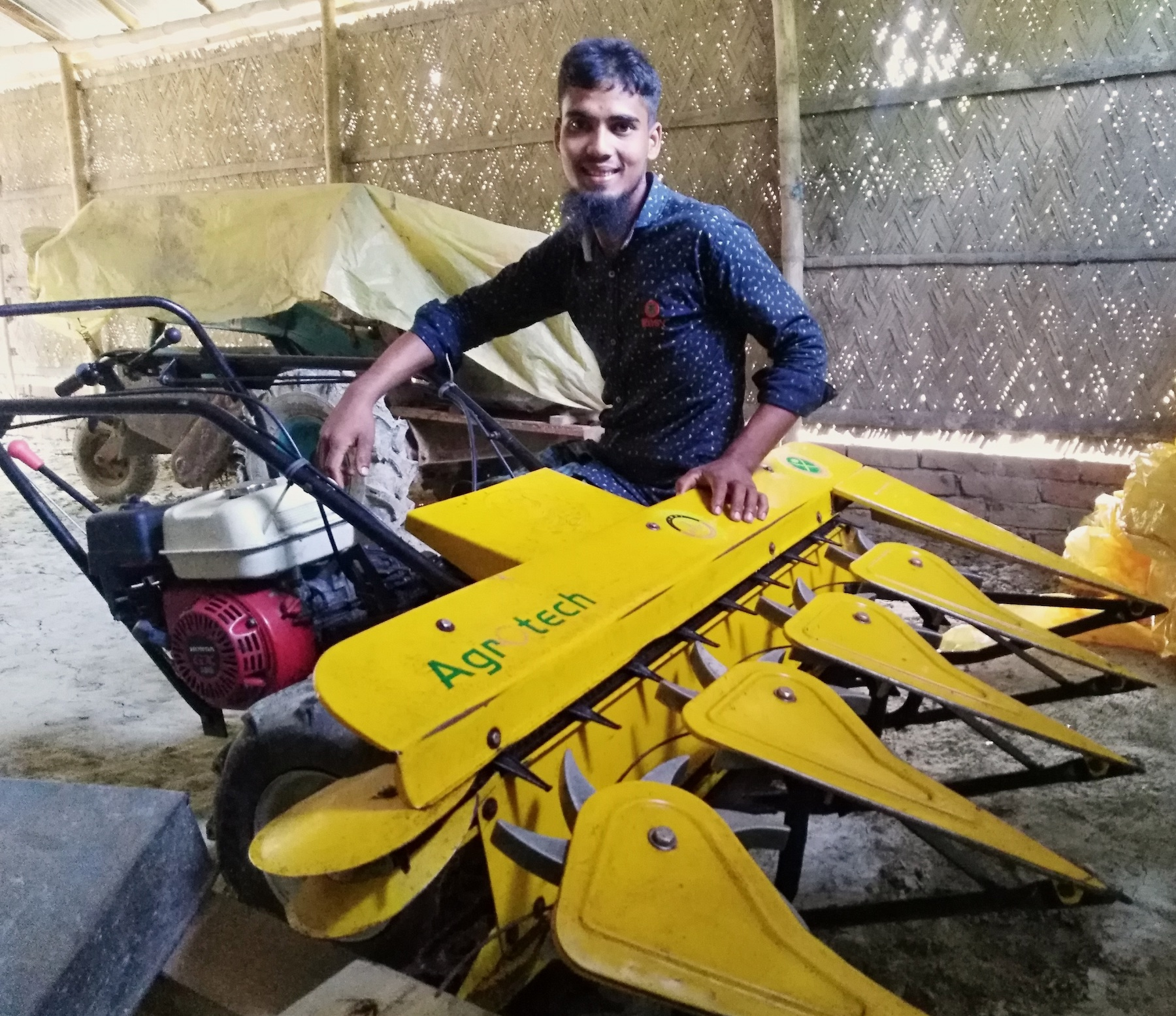 Bangladesh farmer Raju Sarder sits on his recently acquired reaper. (Photo: CIMMYT/Md. Ikram Hossain)