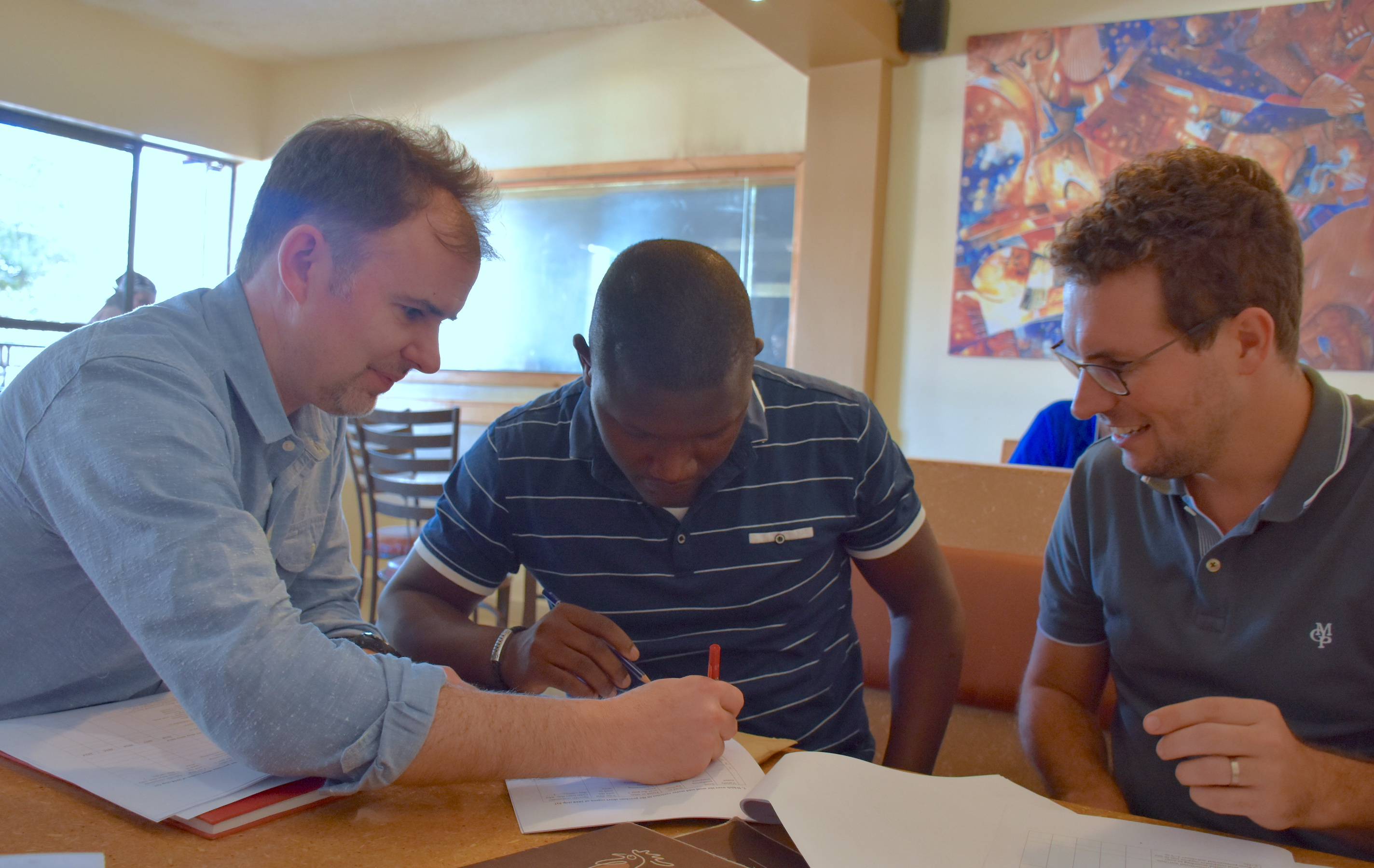 CIMMYT researchers Jason Donovan (left) and Pieter Rutsaert (right) discuss the research study questionnaire with consultant enumerator Victor Kitoto. (Photo: Jerome Bossuet/CIMMYT)