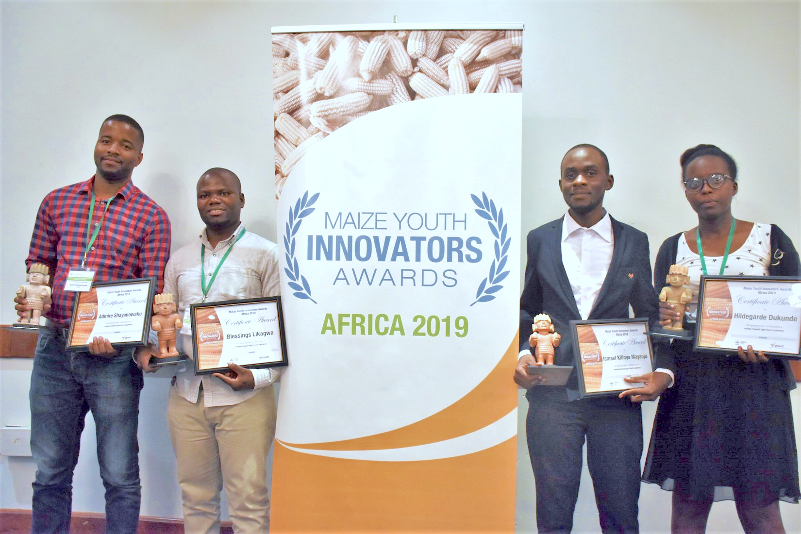 Winners of the 2019 MAIZE Youth Innovators Awards – Africa receive their awards at the STMA meeting in Lusaka, Zambia. From left to right: Admire Shayanowako, Blessings Likagwa, Ismael Mayanja and Hildegarde Dukunde. Fifth awardee Mila Lokwa Giresse not pictured. (Photo: J.Bossuet/CIMMYT)
