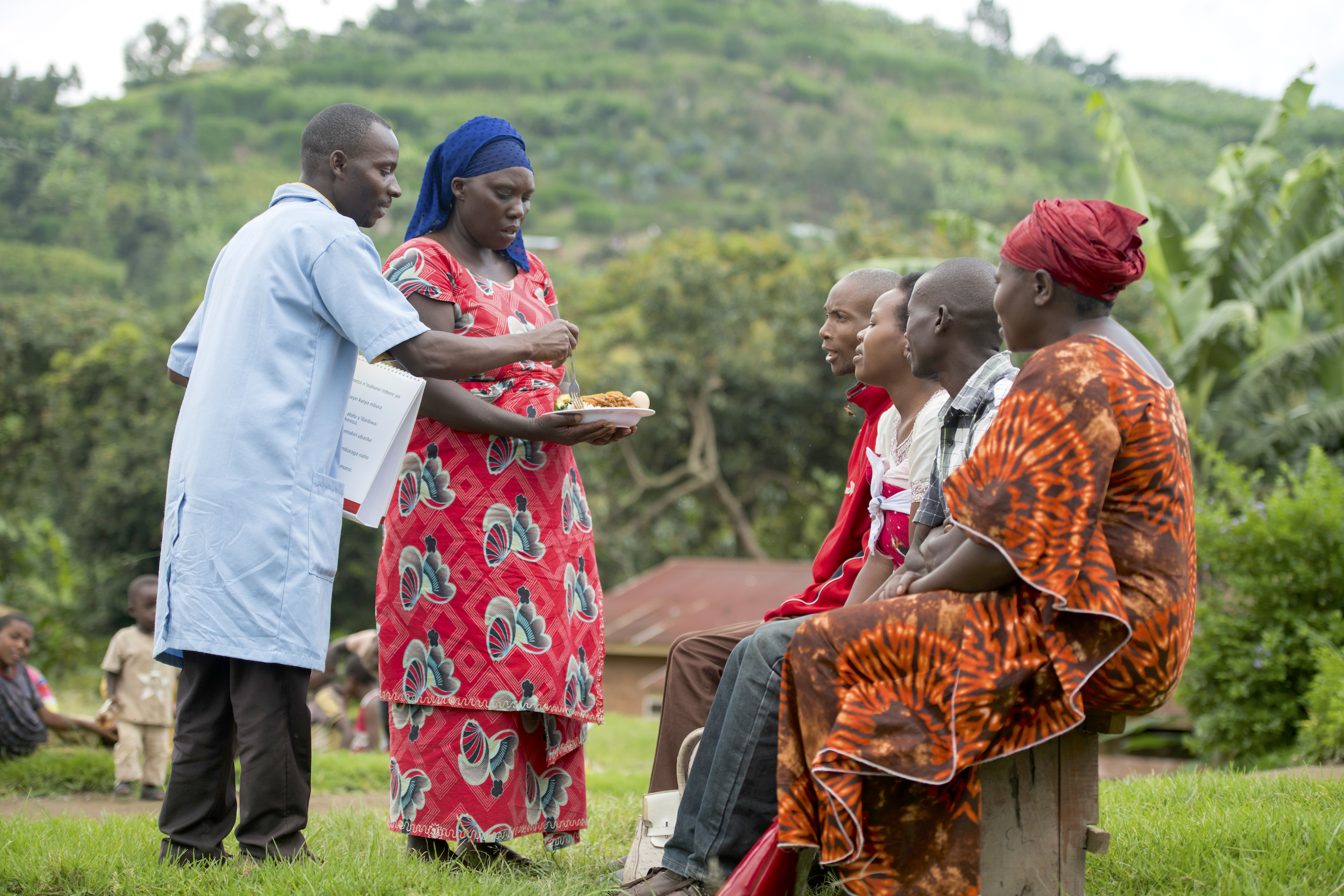A community health worker in Rwanda talks to people on hygiene and the importance of a balanced diet, as part of the SUSTAIN project. (Photo: CIP)