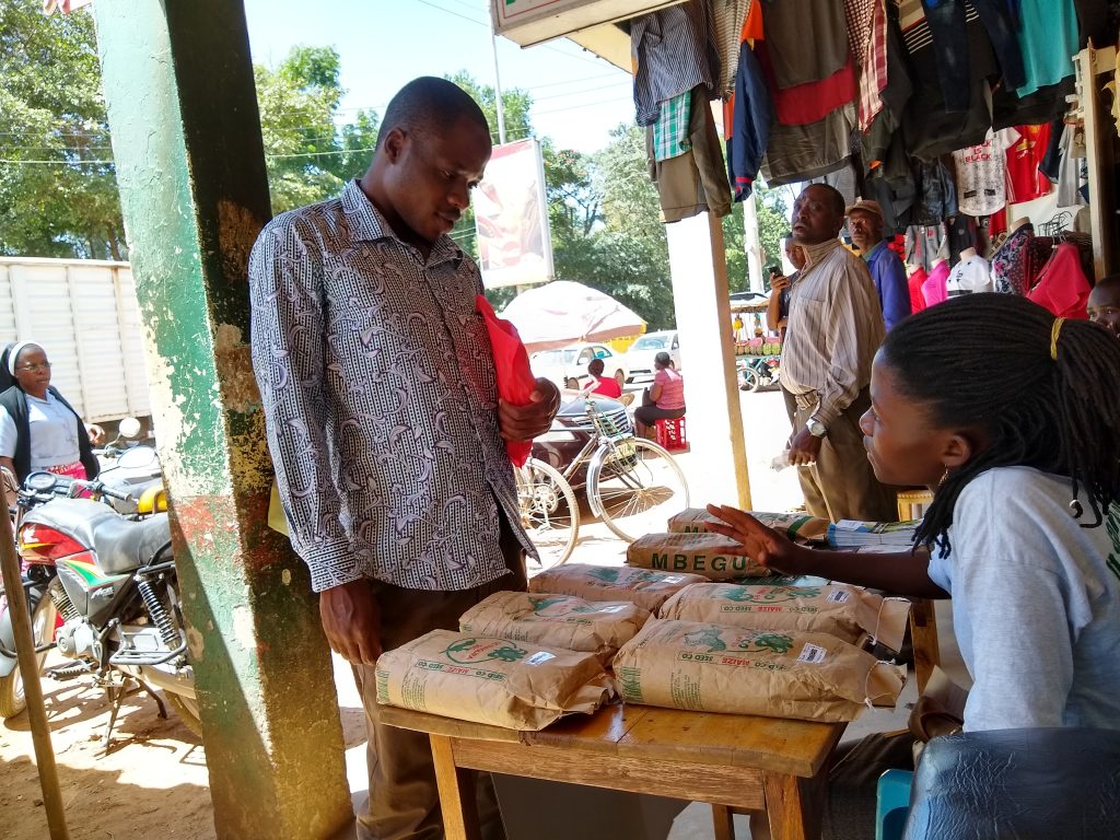 An agent from a seed company (right) promotes sales at an agro-dealer shop. (Photo: Pieter Rutsaert/CIMMYT)