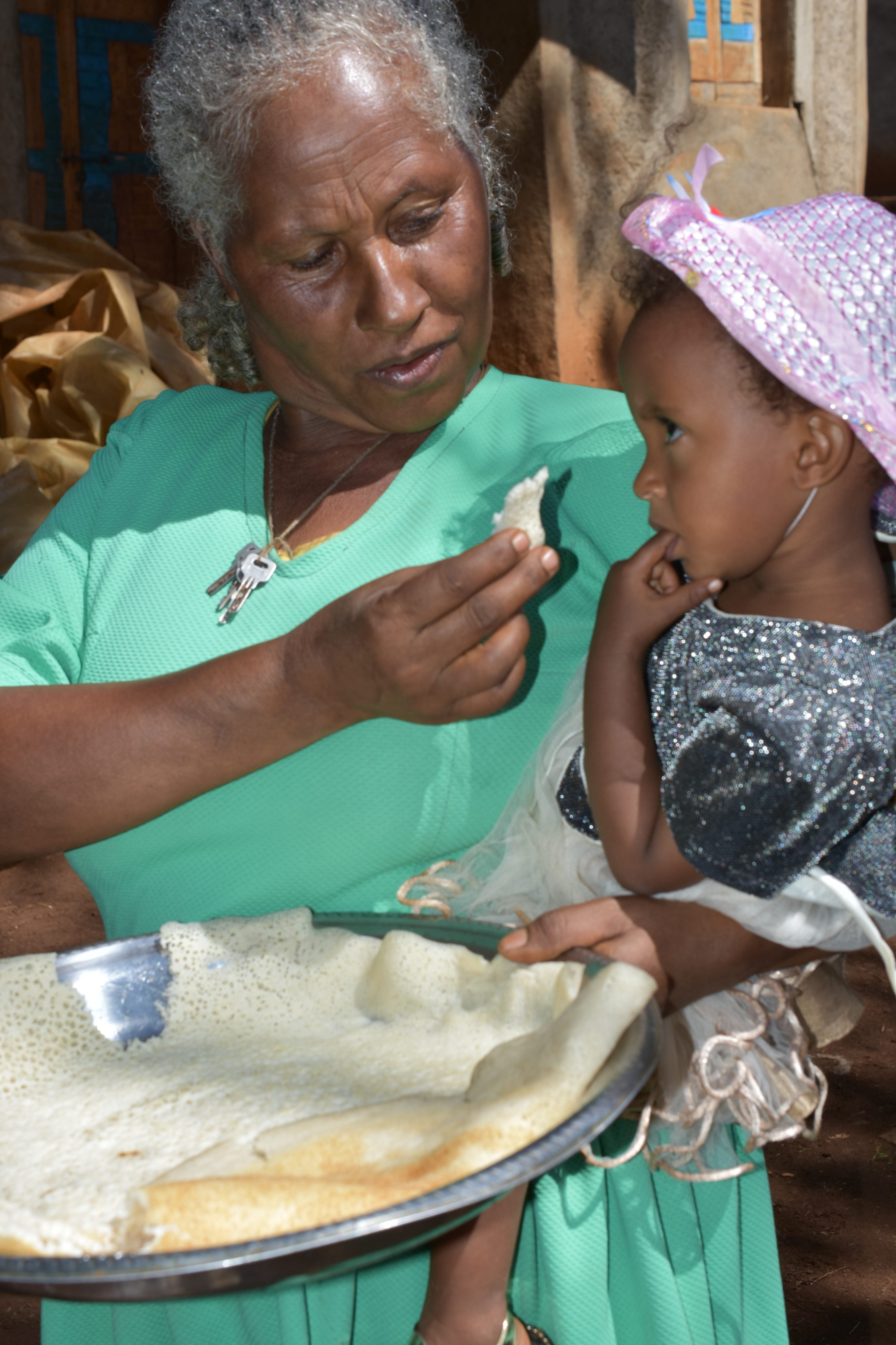 Sequare Regassa feeds her granddaughter with maize injera. (Photo: Simret Yasabu/CIMMYT)