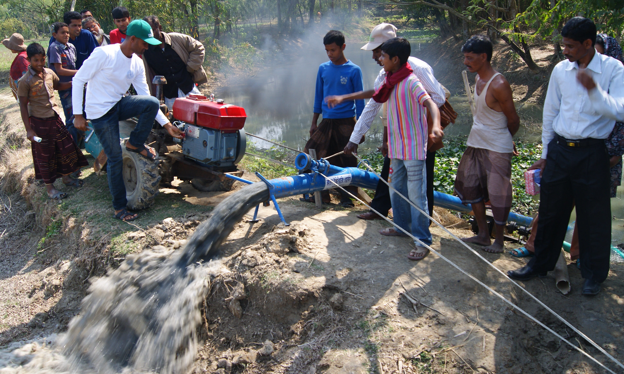 Local irrigation service providers in southern Bangladesh demonstrate the use of a two-wheeled tractor to power an axial flow pump to provide fuel-efficient surface water irrigation. (Photo: Tim Krupnik/CIMMYT)