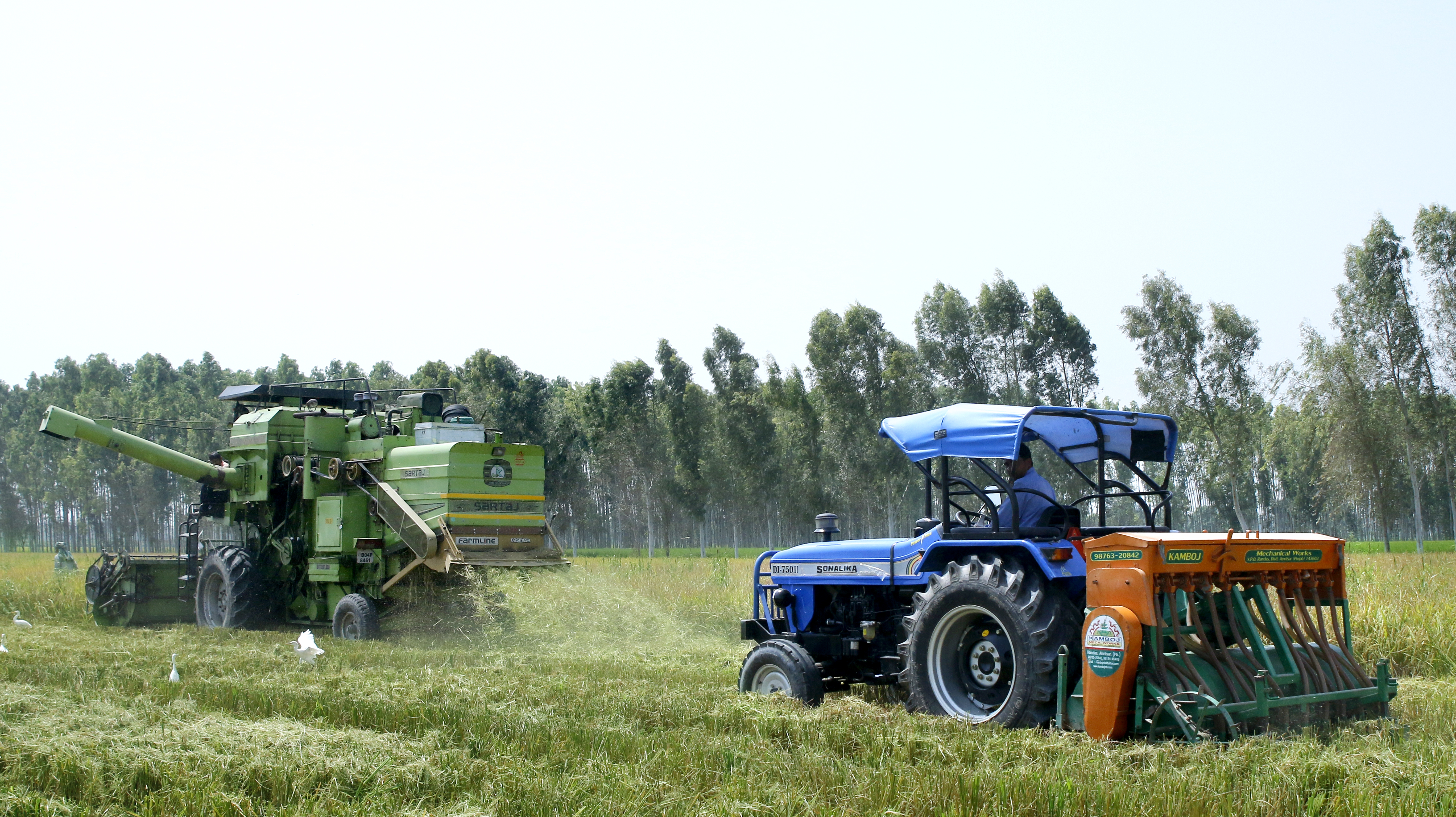 A combine harvester (left) equipped with the Super Straw Management System, or Super SMS, works alongside a tractor fitted with a Happy Seeder. (Photo: Sonalika Tractors)