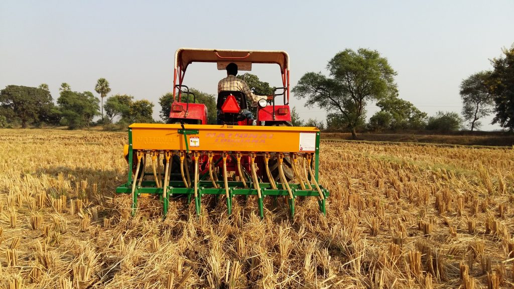 A farmer in India uses a tractor fitted with a Happy Seeder. (Photo: Dakshinamurthy Vedachalam/CIMMYT)