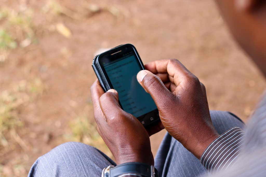 A farmer uses a smartphone to access market information.