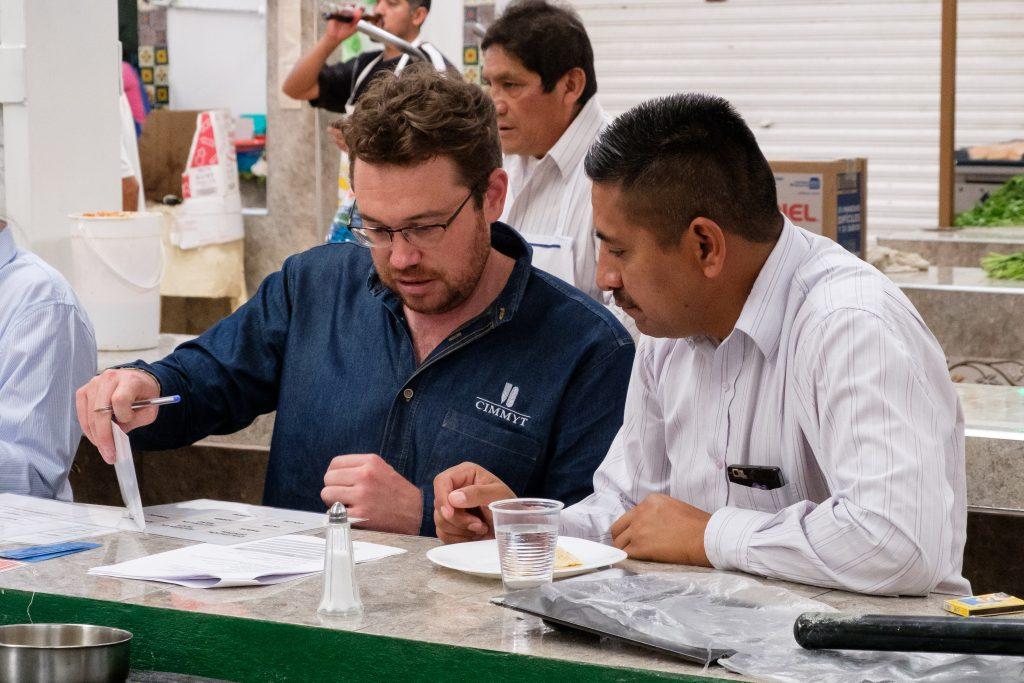 Trent Blare (left), economist at CIMMYT and leader of the study, conducts a choice experiment with interviewee Luis Alcantara. (Photo: Carolyn Cowan/CIMMYT)