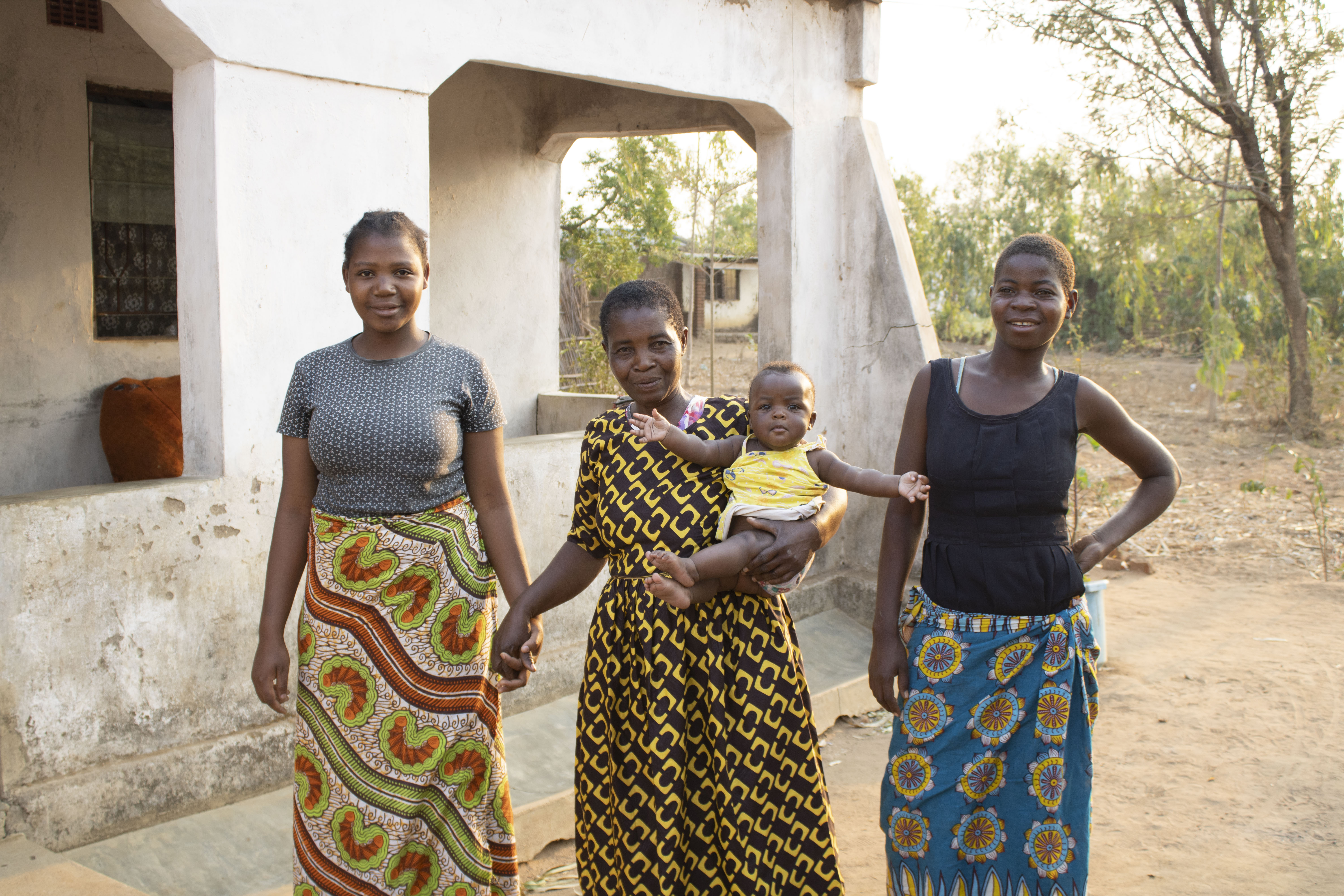 Lughano Mwangonde (center) holds her granddaughter and stands for a portrait with her daughters. (Photo: Shiela Chikulo/CIMMYT)