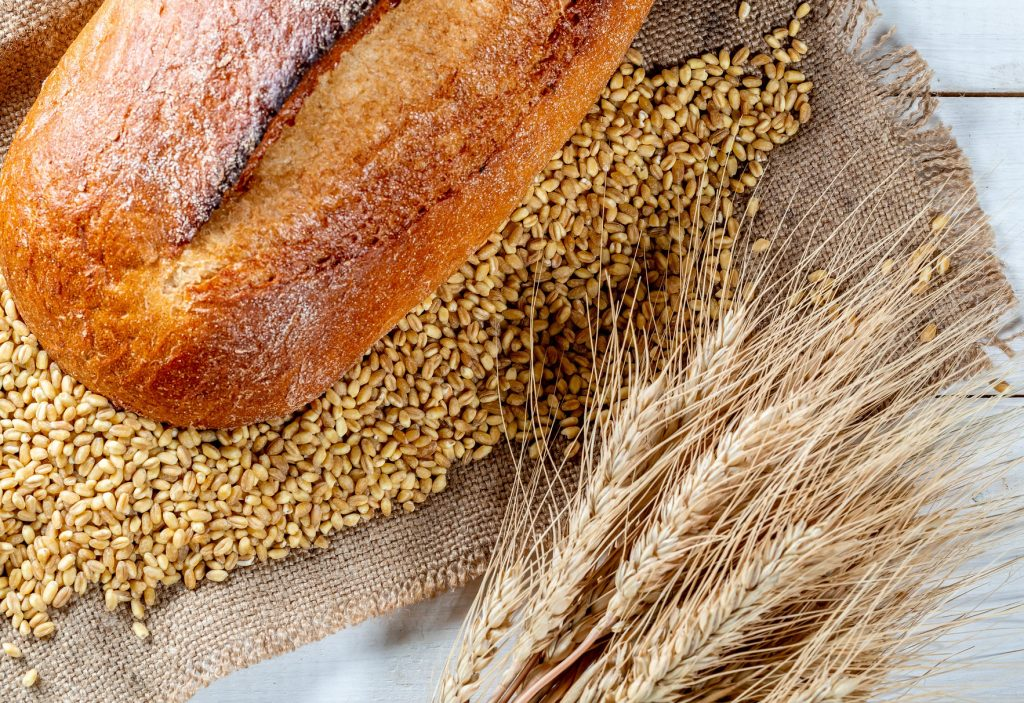 Freshly baked rye bread is displayed next to wheat spikes and grains. (Photo: Marco Verch/Flickr)