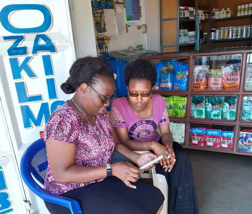 Enumerator Mary Mdache (left) interviews Shangwe Stephano, staff of BAYDA agrovet shop in Haydom town, Mbulu district, Tanzania. (Photo: Furaha Joseph)
