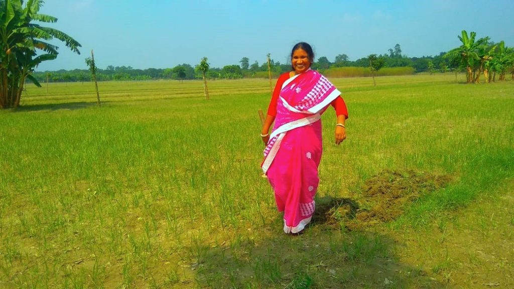 Halima Bibi stands on her field in the district of Malda, West Bengal, India.