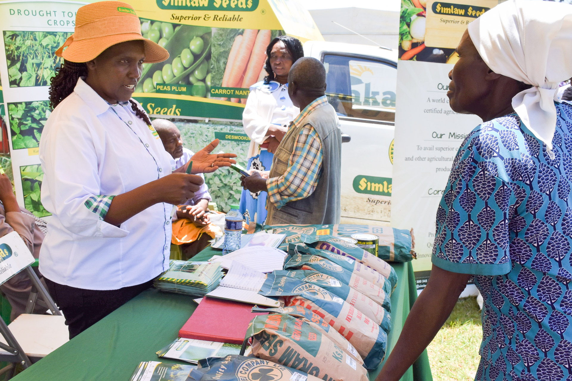 A seed company representative shows seeds to a farmer during the visit to the demonstration farm. (Photo: Joshua Masinde/CIMMYT)