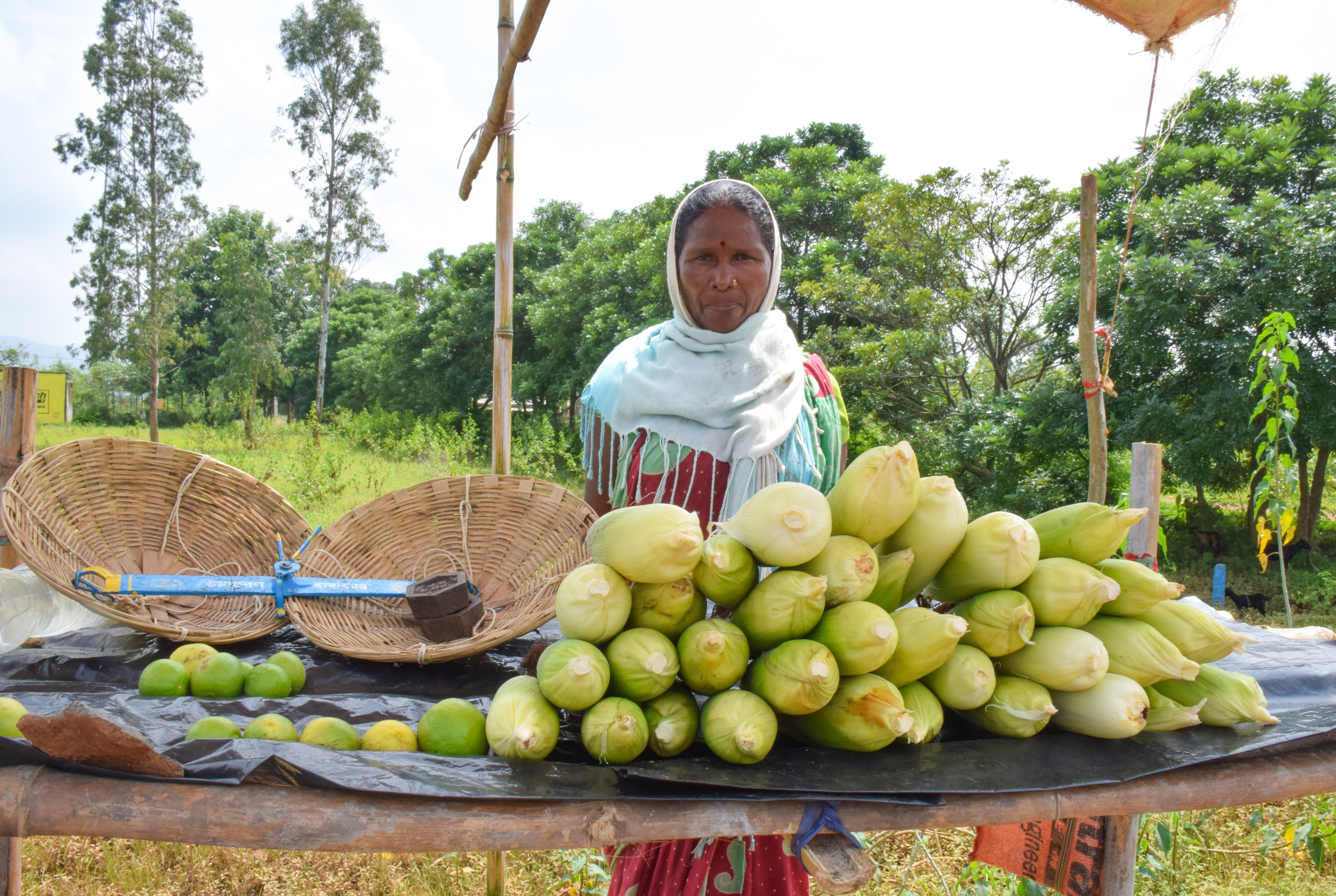 Women shows off maize stall.