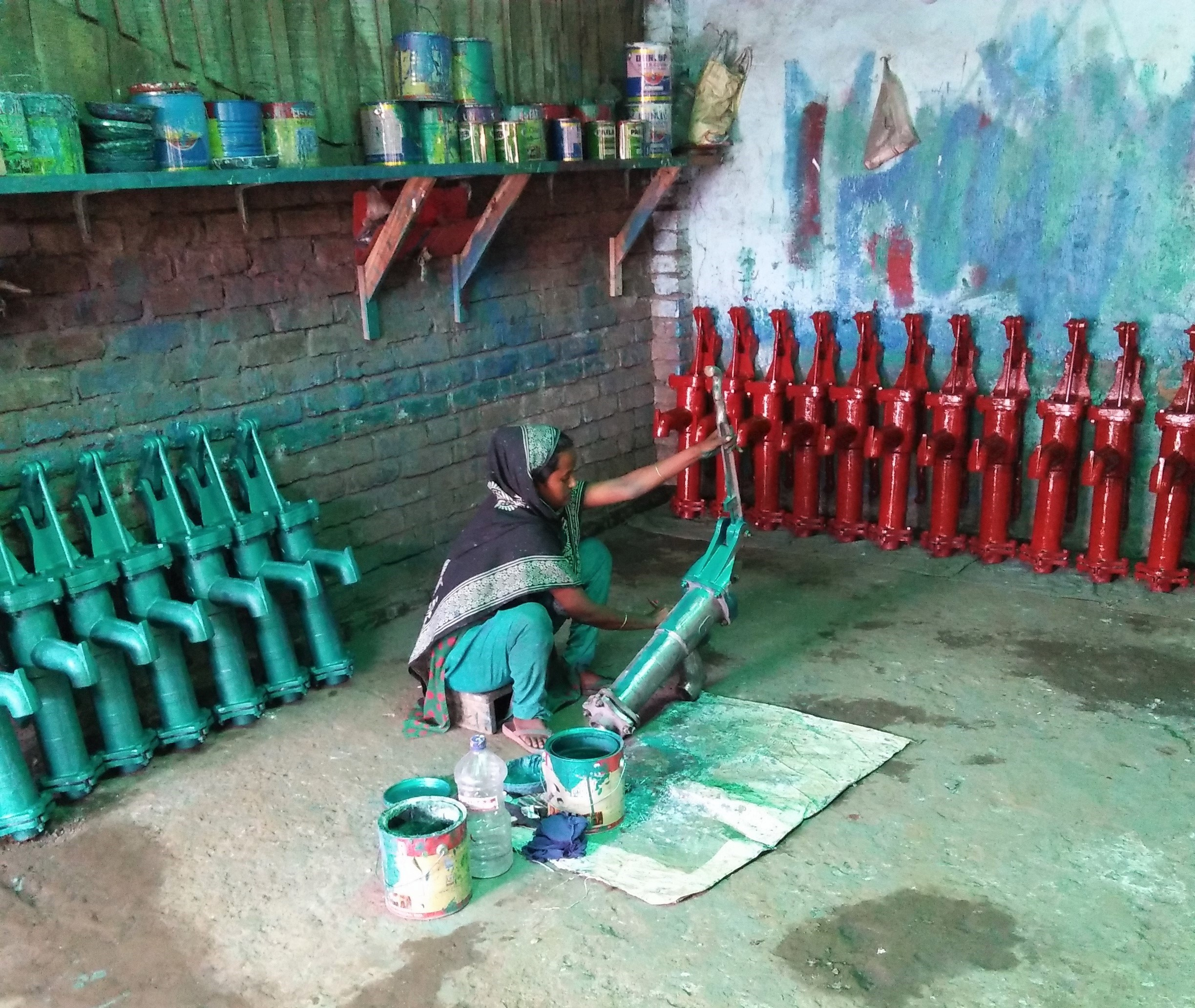 Woman paints machinery.