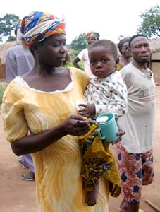 Throughout the developing world, 32% of children under the age of five are stunted and 20% are underweight. Improving the quality of protein in maize can help alleviate this problem in areas where people eat a lot of maize. Here a mother feeds her child QPM during a QPM feeding program hosted by Self-Help International in Ghana.