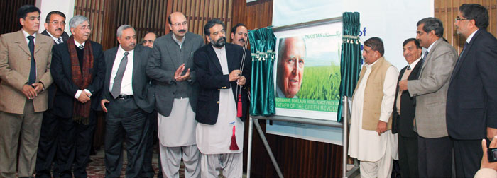 Mr. Sikhandar Hayat Khan Bossan, Federal Minister for Food Security and Research, Pakistan, unveils a new stamp to commemorate the 100th birthday in 2014 of late wheat scientist and Nobel Peace Prize Laureate, Dr. Norman E. Borlaug. Photo: Amina Khan/CIMMYT
