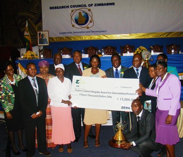 El Programa de Mejoramiento de Maíz de Zimbabwe recibe el premio Robert Gabriel Mugabe a lo más destacado de la investigación durante el 10o Simposio Internacional de Ciencia, el 13 de febrero de 2015. De izq-der: G. Magombo (Director Ejecutivo de ZERA); D. Kutywayo; O. Muchinguri-Kashiri (Ministro de Enseñanza Superior y Avanzada, Desarrollo Ciencia y Tecnología); M.J. Tumbare; T. Chigama; P. Mphoko (Vicepresidente de la República de Zimbabwe); P. Mabodza; E.D Mnangagwa (Vicepresidente de la República de Zinbabwe); C. Mutimaamba; V. Tamirepi (sostiene el trofeo); P. Mazibuko; Prof I. Sithole-Niang; R. Mukaro Foto: Departamento de Investigación y Servicios Especializados, Ministerio de Agricultura, Mecanización y Desarrollo del Riego