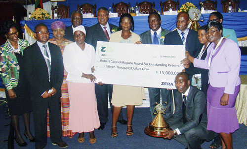 The Zimbabwe Maize Breeding Programme receives the Robert Gabriel Mugabe Award for Outstanding Research, at the10th Zimbabwe International Research Symposium, 13 February 2015. From left to right: Eng.G. Magombo (ZERA Chief Executive Officer); D. Kutywayo; Honorable O. Muchinguri-Kashiri (Zimbabwe Minister of Higher & Tertiary Education, Science &Technology Development); Dr. M.J. Tumbare; T. Chigama; P. Mphoko (Vice-President of the Republic of Zimbabwe); P. Mabodza; Honorable E.D Mnangagwa (Vice-President of the Republic of Zimbabwe); Dr. C. Mutimaamba; V. Tamirepi (holding trophy); P. Mazibuko; and Prof. I. Sithole-Niang; R. Mukaro. Photo: Courtesy of IBP