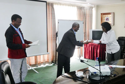 Ms. Elsa Asfaha (right), Manager, Alamata Agroprocessing, receives her certificate from Tafesse Gebru (middle), the Chief Executive Officer of the Ethiopian Seed Enterprise, while Adefris Teklewold (left), NuME project leader, looks on.