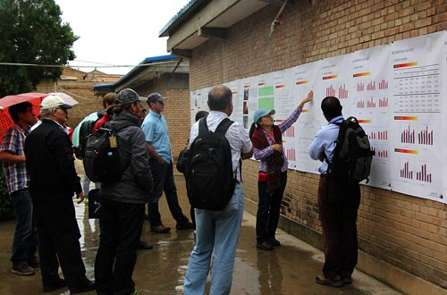 Li Lingling presents her 14 years of trial data on a 16-m wall poster in drizzling rain to the international attendees at Dingxi Research Station. Photo: Jack McHugh/CIMMYT