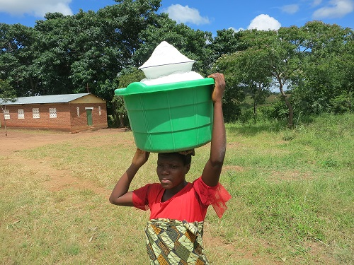 Young lady carrying home flour from millers, Salina, Malawi. Photographer: Tsedeke Abate/ CIMMYT