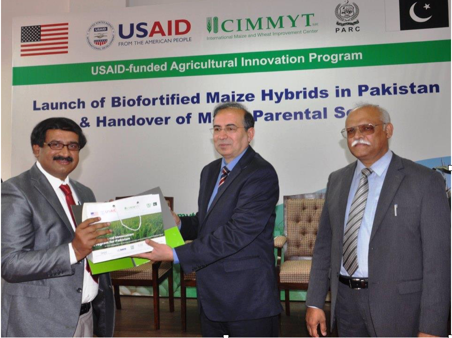 M. Hashim Popalzai (center) handing over samples of maize parental lines. At the left Mr. Faisal Hayat from the seed company Jullundur Private Ltd. receiving the seed and at the right Nadeem Amjad, PARC Chairman. Photo: M. Waheed Anwar