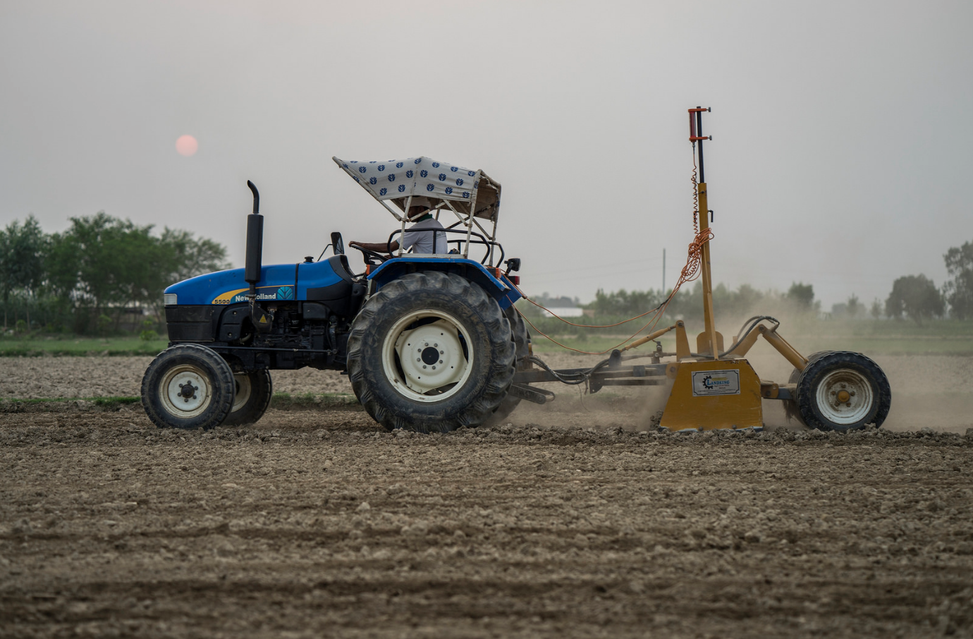 Farmer Krishna Chandra Yadav laser levels land for rice planting in Sirkohiya, Bardiya. Laser leveling is one of many climate-friendly tools that conserves water and helps farmers plant their crops more precisely and efficiently. Photo: P.Lowe/CIMMYT