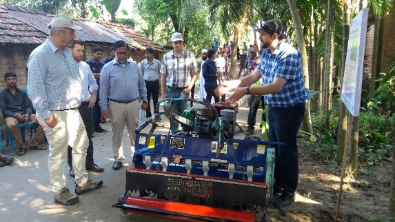 Timothy Krupnik (right) explains the use and benefits of the Power Tiller Operated Seeder to USAID Deputy Administrator Gary Lindon (far left). Photo: Md. Aktarul Islam/CIMMYT-Bangladesh