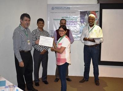 Suma Karki from Seed Quality Control Center (SQCC) of Nepal receiving certification of participation Photo: E. Kohkar/CIMMYT-Pakistan.