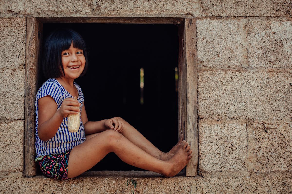 Rómulo González's daughter holds a corncob. (Photo: Sarah Caroline Mueller)