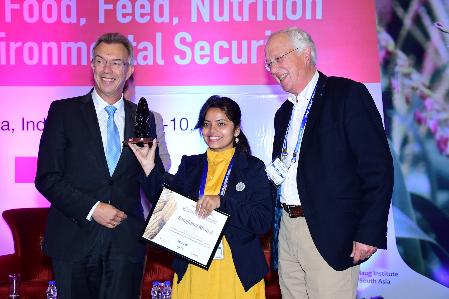 The Director General of CIMMYT, Martin Kropff (left), and the Chair of the MAIZE Independent Steering Committee, Michael Robinson (right), present Samjhana Khanal with the 2018 MAIZE-Asia Youth Innovator Award in the category of Change Agent. (Photo: Manjit Singh/Punjab Agricultural University)