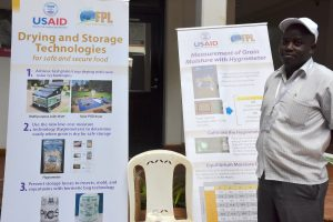 A workshop participant stands by banners with information about low-cost hygrometers. (Photo: Joshua Masinde/CIMMYT)