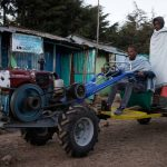 Service provider Bedilu Desta and his helper Fekadu Assefa drive a two-wheel tractor and thresher in the village of Gudoberet, Basona district, Ethiopia, in 2015. (Photo: Peter Lowe/CIMMYT)